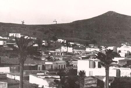 El pueblo de Haría en 1895 y, sobre la lomada de La Atalaya, la molina y el molino a los que se iba por este sendero./ ARCHIVO DE FOTOGRAFÍA HISTÓRICA DE CANARIAS-FEDAC
