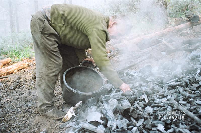4. Tras enfriarlo un poco y aunque todavía humea, Nardo empieza a coger el carbón para ponerlo en los sacos en los que se los llevará. | FOTO YURI MILLARES